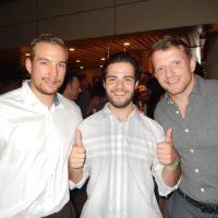 Canucks players Sven Bartschi, left, and Derek Dorsett with Christian Aquilini, centre